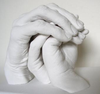 Gipsabformungen von drei sich beschützenden Händen einer Familie