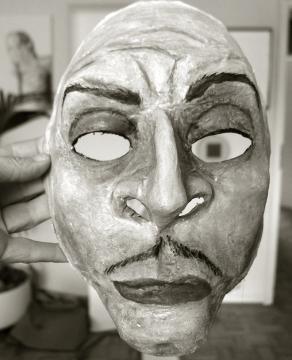 Foto einer Maske, in der Hand gehalten