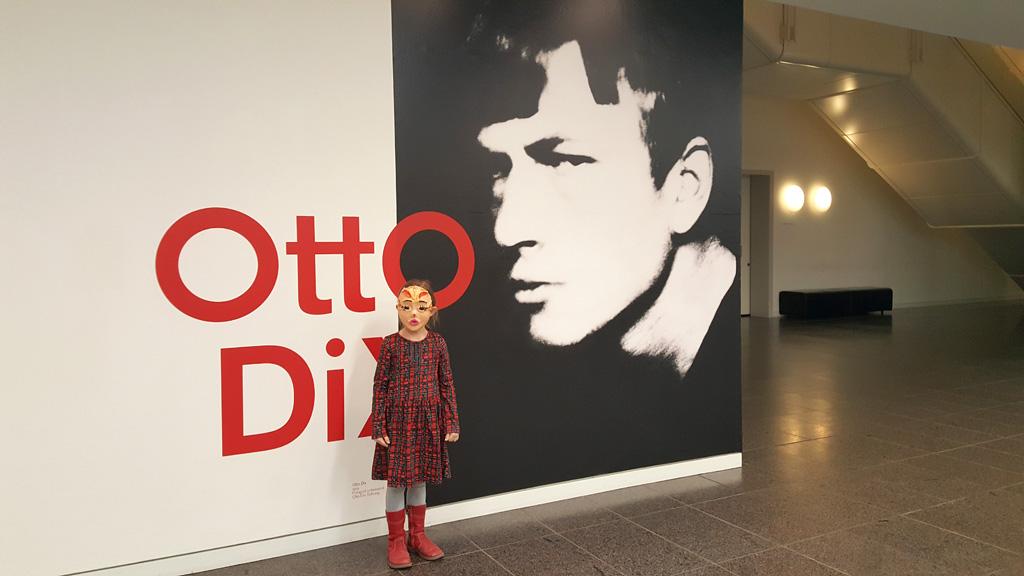 Foto: Mädchen mit Maske vor Otto-Dix-Plakat